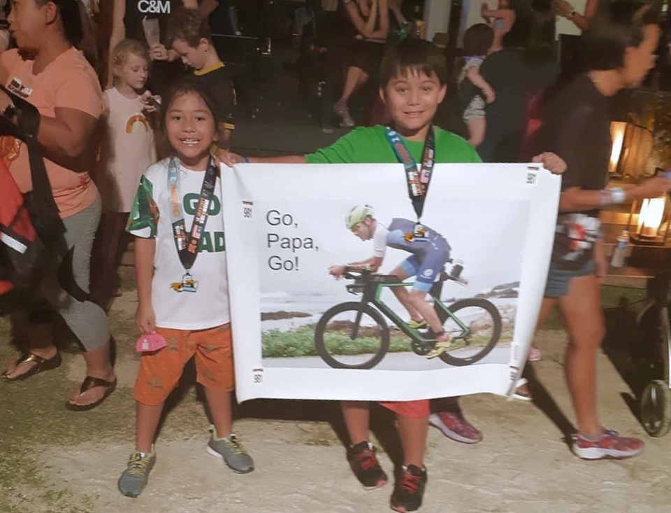 "Kids holding up poster saying, ""Go, Papa, Go!"" at an Ironman race"