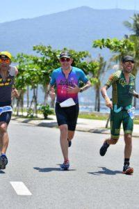 3 triathletes running in the sun