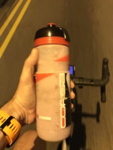 hand holding a bottle while on a bike