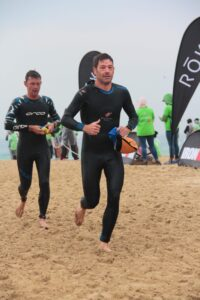 Ironman athletes exiting the water and running on a beach after a swim